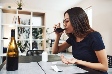 Addicted woman taking drugs with alcohol
