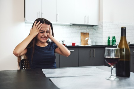 "Addiction begins with the hope that something ""out there"" can instantly fill up the emptiness inside. Young addicted, depressed woman with red wine sitting in the kitchen, holding her head in despair"