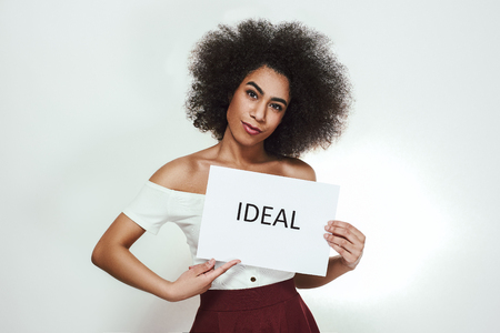 Studio portrait of confident young afro american woman holding a paper which is saying Ideal while standing against grey background