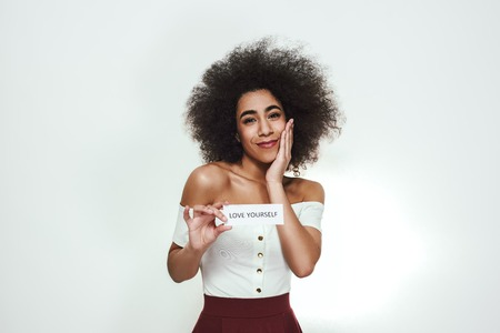 Positive and happy afro american woman with curly hair holding a sheet of paper which is saying Love yourself while standing against grey background.