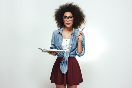 Confident young african woman in eyewear holding her notebook and pen and looking at camera while standing against grey background