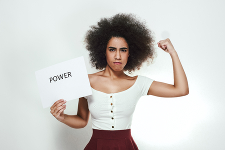 Confident young afro american woman showing how strong she is and holding a paper which is saying Power.