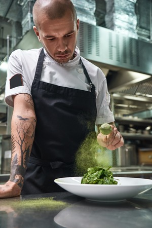 Vertical portrait of handsome male chef in black apron adding spices in salad Stock Photo