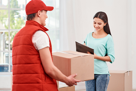 Woman signing receipt of delivery package. Stock Photo