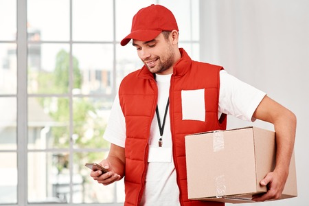 Cheerful postman holding parcels and looking for customer number