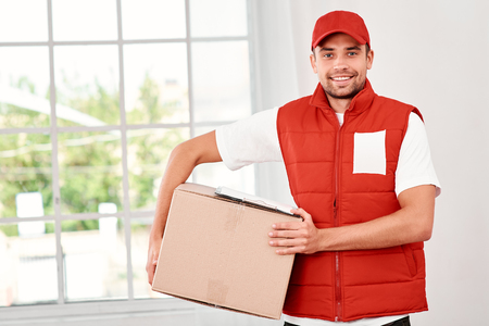 Image of a happy young delivery man standing with parcel box indoors 写真素材