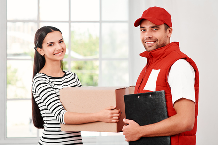 Young woman receiving parcel from delivery man Stock Photo - 119349644