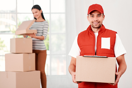 Woman receiving parcels from delivery service courier, indoors Stock Photo - 119349706