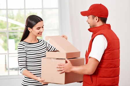Young woman receiving parcels from delivery man Stock Photo - 120898594