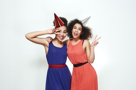 Party celebration. Portrait of two positive and young afro american women in beautiful evening dresses and party hats are showing peace sign and laughing