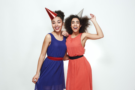 Birthday party! Two cute and young afro american women wearing summer dresses and party hats celebrating a birthday while standing against grey background Imagens