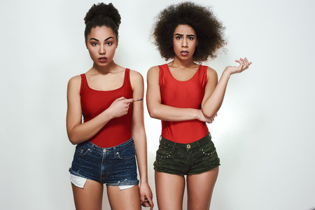 Its her fault! Studio shot of disappointed afro american woman in jeans shorts pointing index finger at her friend while standing against grey background. Zdjęcie Seryjne