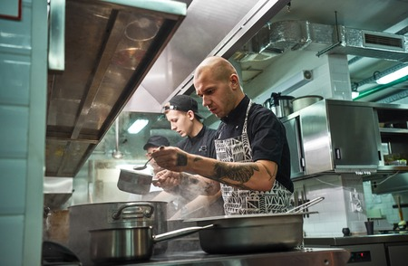 Busy working day. Professional team of restaurant chef and his two young assistants cooking at modern kitchen Reklamní fotografie - 120918990