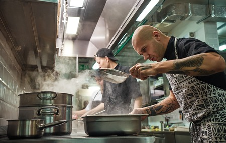 Restaurant kitchen. Professional chef in apron, with tattoos on his arms is sifting the flour while cooking with his two assistants