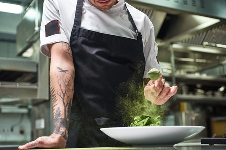 Slow motion. Cropped image of chefs hands with tattoos adding spices in salad while standing in a restaurant kitchen.