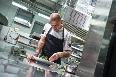 Food concept. Portrait of handsome professional chef in black apron decorating a salad on the plate while working in restaurant kitchen Stockfoto