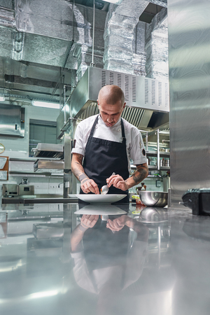 Working in a restaurant. Vertical portrait of professional male chef with tattoos on his arms garnishing his dish on the white plate