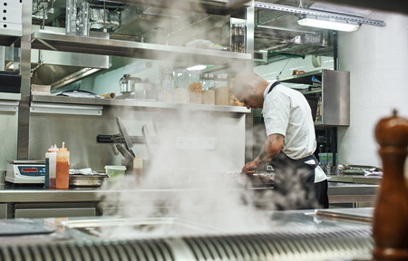 Busy day. Back view of male chef in apron cutting a meat while standing in a restaurant kitchen Reklamní fotografie