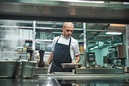 I should be careful. Serious male chef with several tattoos on his arms holding a frying pan above the oven in a restaurant kitchen