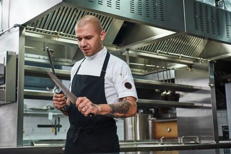 Everything should be perfect Brutal chef with several tattoos on his arms sharpening a knife while standing in a restaurant kitchen 写真素材