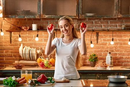 I guess I fell into cooking. Happy young woman cooking vegetables in modern kitchen. Cozy interior Banco de Imagens