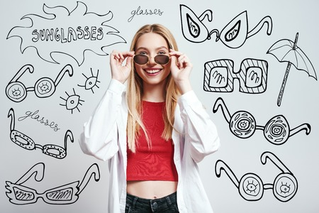Beauty in sunglasses. Stylish and cheerful blonde woman in casual clothes wearing sunglasses while standing against grey background with hand drawn doodles on it. Фото со стока