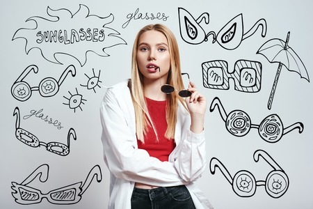 In her own style. Pretty blonde woman holding sunglasses and looking at camera with open mouth while standing against grey background with hand drawn doodles on it.