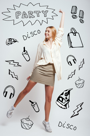 I am going at disco! Full length of beautiful blonde woman smiling and gesturing while standing against grey background with party theme doodles on it. Party