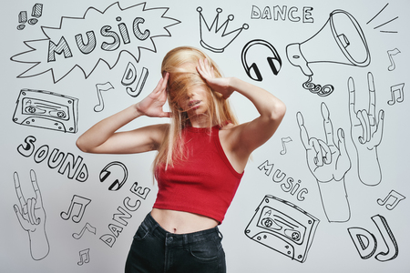 Funky mood. Close up portrait young woman in red tank top covering face with her hair while standing against grey background with music theme doodles.