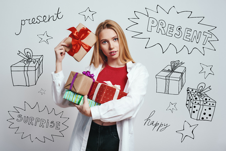Birthday presents. Close up of cute young woman in white shirt carrying gift boxes while standing against grey background with different themed doodle illustrations on it