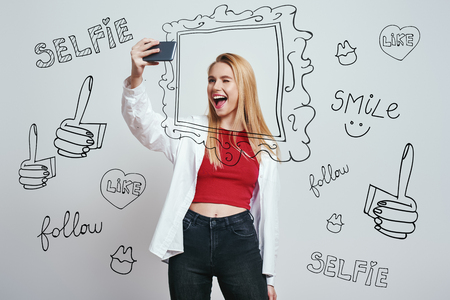 Cheerful young woman with blond hair making selfie by her smartphone and giving a wink while standing against grey background with different hand drawn doodle illustrations on it.