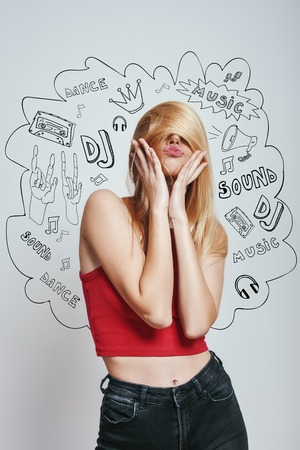 Going crazy. Young woman in in red tank top covering face with her hair and making funny face while standing against grey background with music theme doodles. Stock Photo