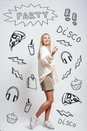 Positive girl. Full length portrait of cheerful blonde woman smiling and gesturing while standing against grey background with party theme doodles on it. Party