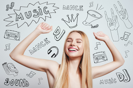 DJ party. Happy young blonde woman with naked shoulders smiling with raised hands while standing against grey background with music theme doodles 版權商用圖片
