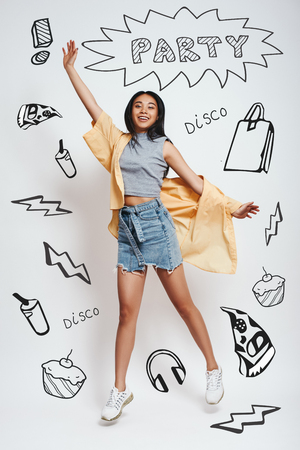 Going crazy! Happyyoung asian woman smiling and jumping against grey background with party theme doodles on it. Stock fotó