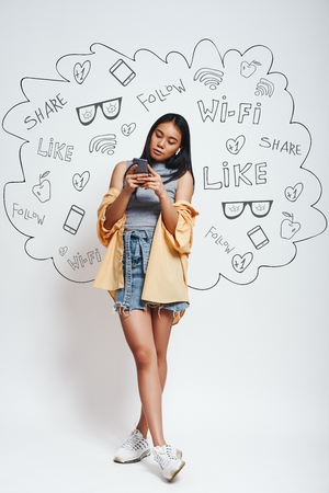 Using social media. Full length portrait of pretty asian woman looking at her smart phone while standing against grey background with different doodle illustrations on it.