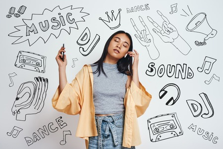 Enjoying her favourite song. Attractive and young asian woman in casual wear listening music with closed eyes while standing against grey background with music theme doodles.