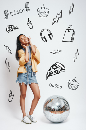 Favourite song. Full length portrait of smiling asian woman with closed eyes listening music and standing near silver disco ball against grey background with different doodle illustrations on it Stock fotó