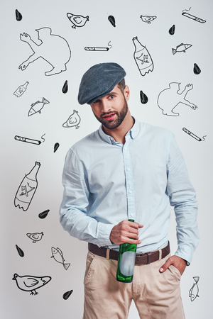 Bad boy. Bearded brutal man in hat holding a beer and looking ar camera while standing against grey background with hand drawn doodles on it. Stock Photo