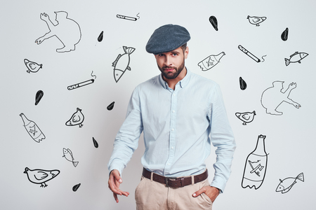 Russian mafia. Brutal bearded man behaving and gesturing like a mafia standing against grey background with hand drawn doodles on it. Stock Photo