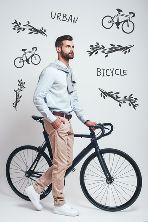 Convenient way to travel. Full length of a modern looking man with beard pulling his bicycle while standing against grey background with hand drawn doodles on it. Urban style