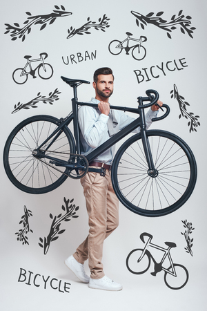 Always with my bike! Full length of good looking man in casual clothes carrying his black bicycle while standing against grey background with hand drawn doodles on it. Urban style