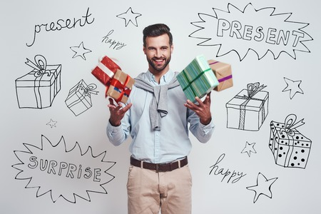 Gifts boom! Cheerful young man is holding gifts and feeling so happy while standing against grey background with different doodle illustrations on it Stok Fotoğraf
