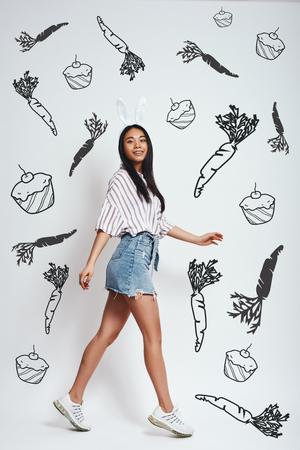 Happy bunny. Full length portrait of young asian woman in bunny ears is smiling while standing against grey background with hand drawn carrots and cupcakes on it