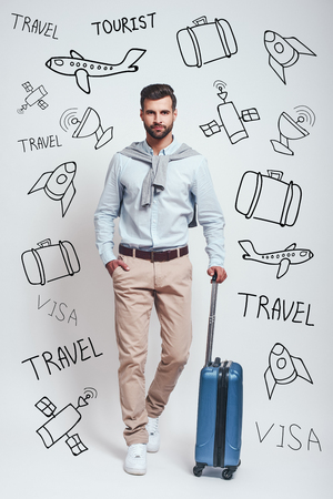 Time for adventure. Full length of charming bearded young man waiting for a flight with his luggage while standing against grey background with doodles on the theme of travel.