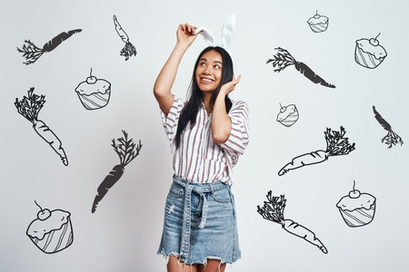 Doing whatever she wants. Young Asian woman in casual clothes touching her bunny ears and smiling while standing against grey background with hand drawn carrots and cupcakes on it