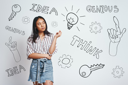 Genius lady. Cute asian young woman in casual wear is thinking and looking at drawn light bulb while standing against grey background with hand drawn doodles on it