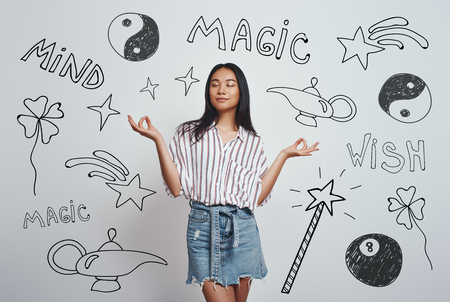 Magic happen. Close up portrait of young asian woman in casual wear meditating and keeping eyes closed while standing against grey background with hand drawn magic tools on it