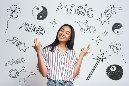 I am making my dreams true. Smiling young asian women in striped shirt holding fingers crossed while standing against grey background with hand drawn magic tools on it Фото со стока