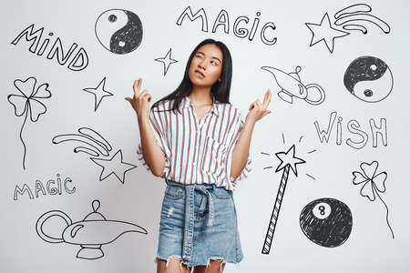 I know magic trick. Cute asian young woman in casual wear crossing fingers and making a wish while standing against grey background with hand drawn magic tools on it